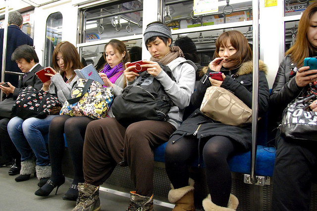 people sat on train looking at their phones