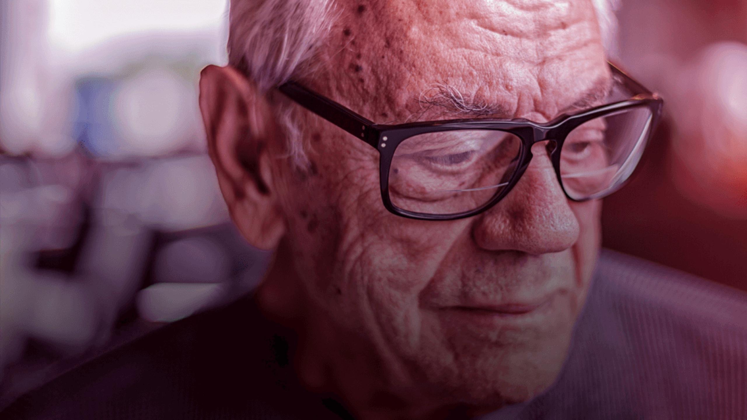 Image of elderly gentleman wearing glasses looking down