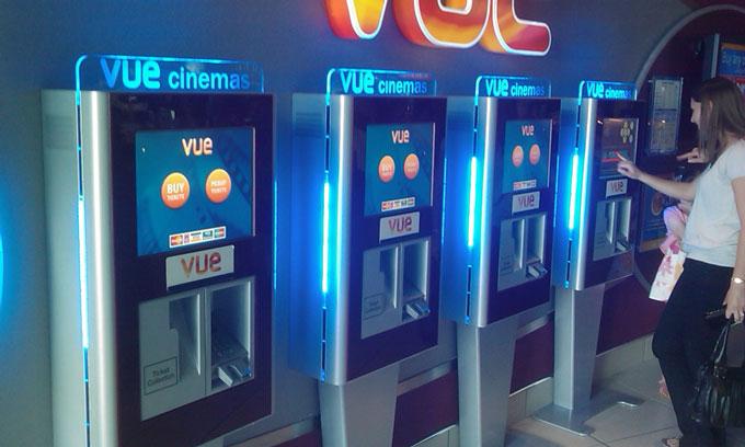 people using self service cinema ticket machines