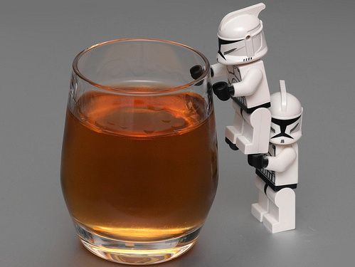 Two storm trooper lego figurines climb into a glass of whisky