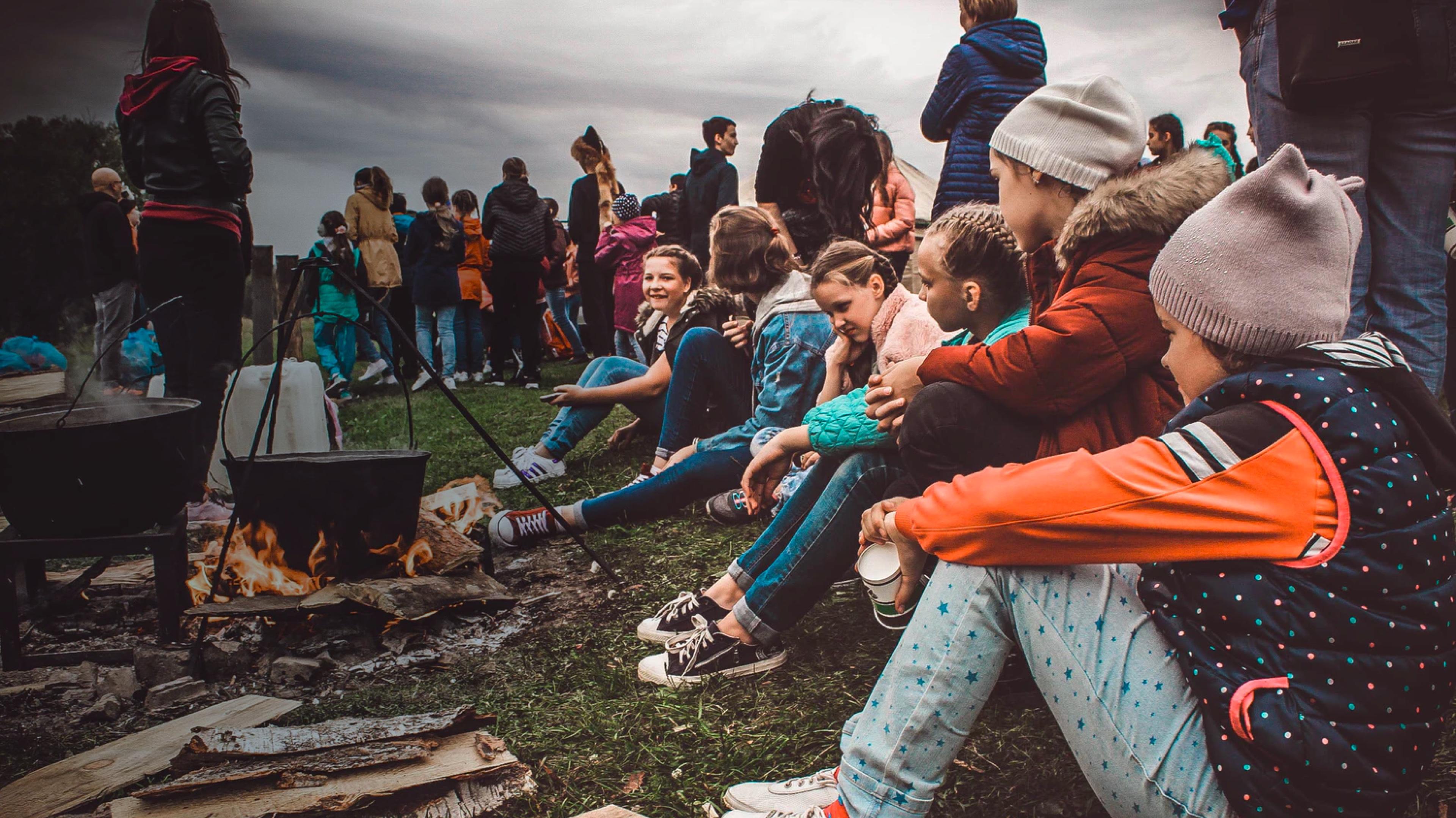 children sat around a camp fire cooking food